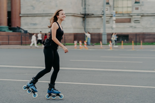 Athletic woman on roller skates moves actively poses on asphalt at street dressed in active wear has cheerful expression. young fitness model skating in urban place. sporty lifestyle rollerblading