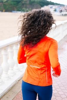 Спортивная (ый) женщина бежит по улице