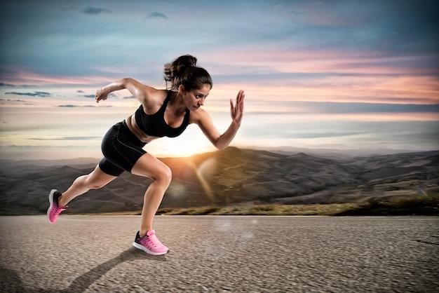 Спортивная женщина быстро бежит по улице во время заката