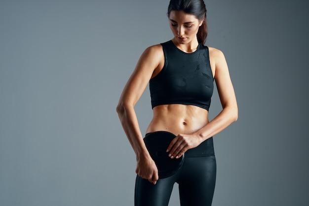 アスレチック女性が筋肉を振るスリムな体型ワークアウトの動機