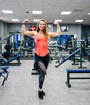 체육관에서 근육을 보여주는 운동 여자. 맞는 여자. 피트니스 모델 전체 길이입니다. 체육관 배경입니다.