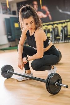 Athletic woman sitting near barbells