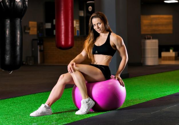 Спортивная (ый) женщина, сидящая на фитнес-мяч