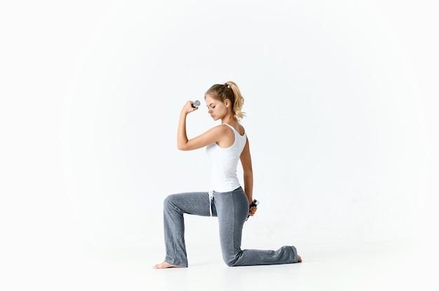 裸足のダンベルトレーニング明るい背景の床に座っている運動の女性