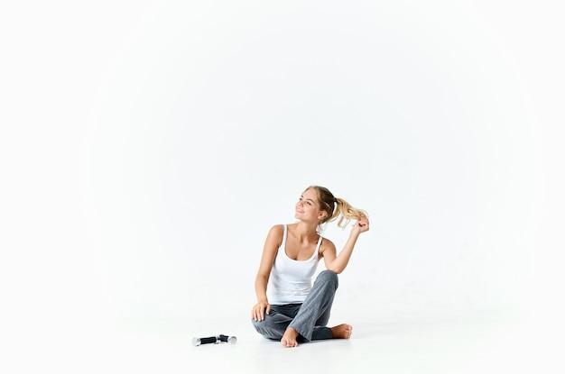 床に座っているアスリート女性ダンベルフィットネスエネルギーモチベーション