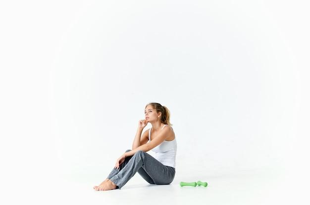 ジムで緑のダンベルのトレーニングと床に座っている運動の女性