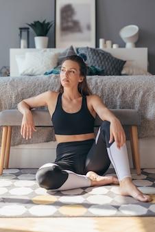 운동 여자는 바닥에 집에서 편안하게 앉아.