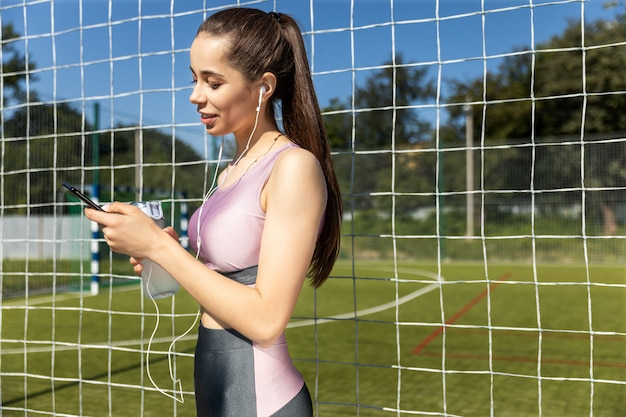 Athletic woman in the sportive outfit is listening music