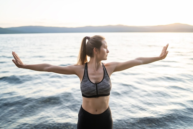 Athletic woman in a sports bra and black leggings stretches before starting classes on the evening shore of the lake