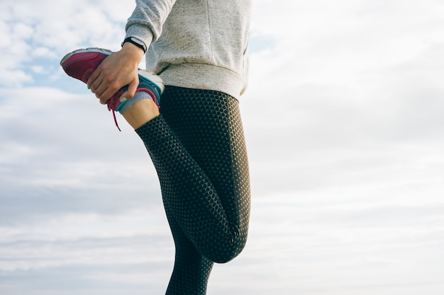 Athletic woman in sportswear doing stretching legs