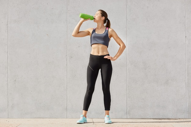 Athletic woman in sportswear drinking water from plastic container while having workout in gymnasiun, keeps hand on hip