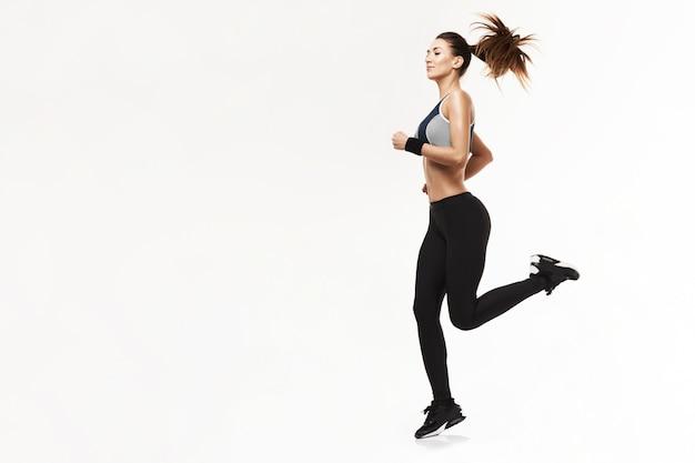 Donna atletica nella formazione di abbigliamento sportivo in esecuzione su bianco.