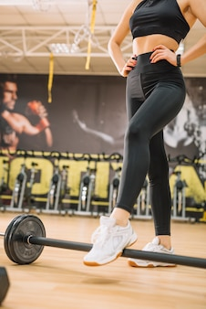 Athletic woman standing near barbells