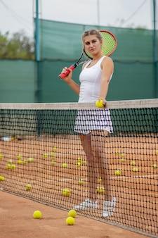 Спортивная (ый) женщина, стоящая возле сети на суде с ракеткой в руках.