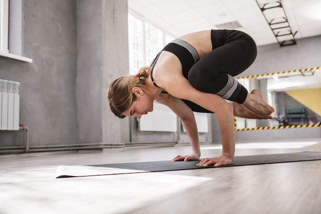 手に立ち、カラスのポーズでバランスをとり、ヨガの練習をする運動の女性