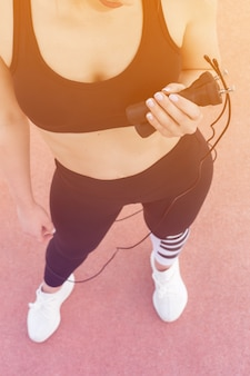 Athletic woman stands and holds in hands with a skipping rope