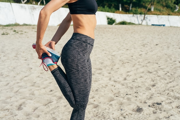 Athletic woman stretches on the beach in the morning