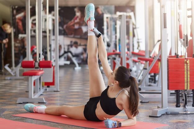 Спортивная женщина, растягивающая ногу на коврике в спортзале, тонизирует мышцы, носит спортивную форму, любит отдыхать после силовых тренировок. фитнес, спорт, обучение и образ жизни концепция.