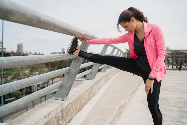 Athletic woman stretching legs before exercise