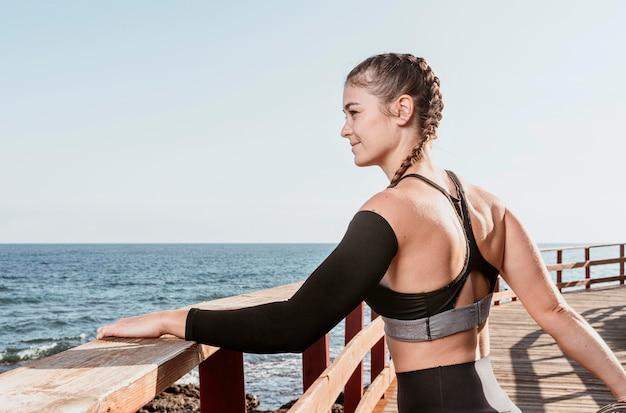 Donna atletica che si estende all'aperto sulla spiaggia con lo spazio della copia