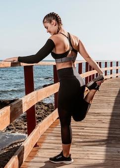 Спортивная (ый) женщина растягивается на пляже