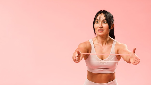 Athletic woman stretching resistance band with copy space