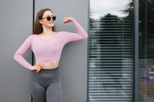 Athletic woman in sunglasses shows biceps