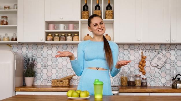 운동 여자는 부엌에서 건강한 식습관에 대해 이야기하고 웃음. 테이블에는 녹색 사과와 스포츠 음료와 물을위한 녹색 병이 있습니다.