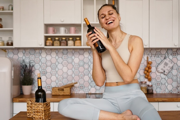 Athletic woman in a tracksuit in a light kitchen drinks red wine from a bottle after doing sports. woman laughs