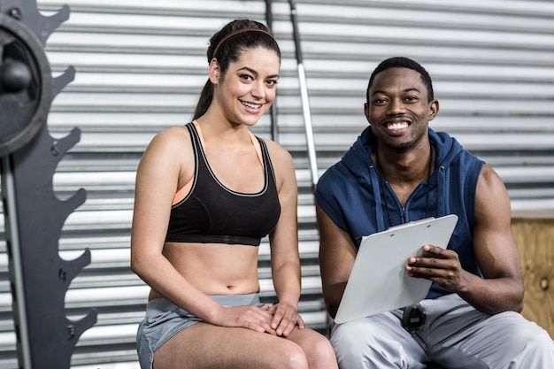 Athletic woman and trainer smiling to camera at crossfit gym