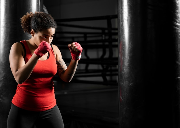 Athletic woman training alone in boxing center