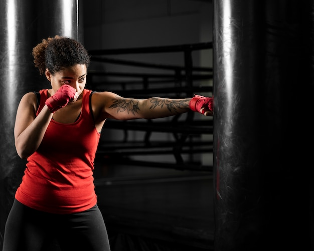 Athletic woman training in boxing center