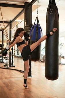 Athletic woman training hard kicking the punching bag