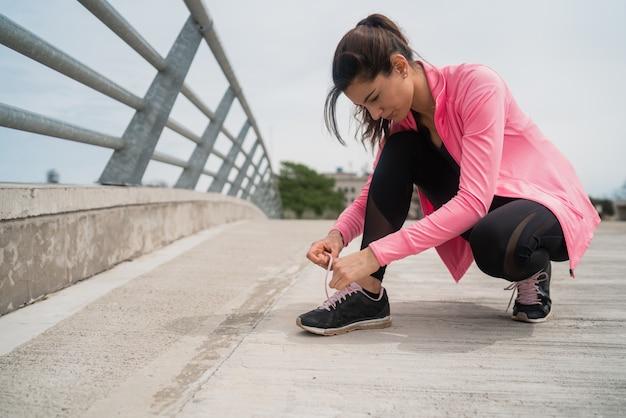 彼女の靴ひもを結ぶ運動の女性