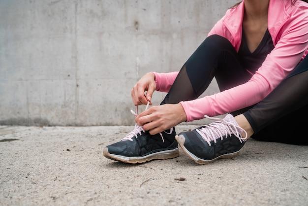 彼女の靴ひもを結ぶ運動の女性。