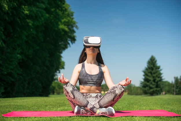 Athletic woman using a virtual reality glasses outdoor