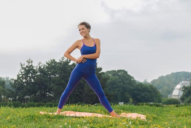 Спортивная женщина в синих леггинсах и спортивной рубашке без рукавов занимается спортом