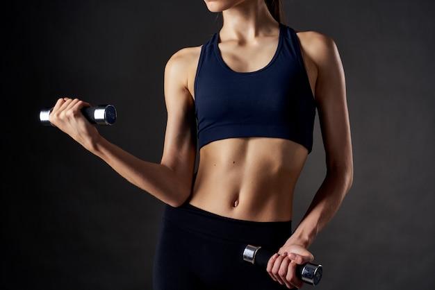 Спортивная (ый) женщина со стройной фигурой с гантелями в руках фитнес-тренировки