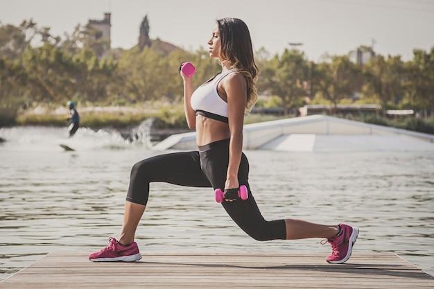Спортивная (ый) женщина с гантелями, разгибающими мышцы на открытом воздухе
