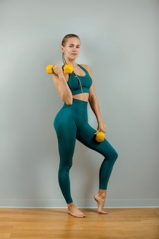 Athletic woman with dumbbells in hands on a gray background, fitness banner, fitness motivation. photo of a muscular fitness model working out with dumbbells on a gray background.