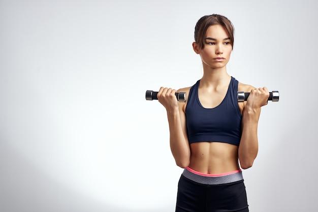 手にダンベルとトレーニングエクササイズ明るい背景を持つ運動の女性