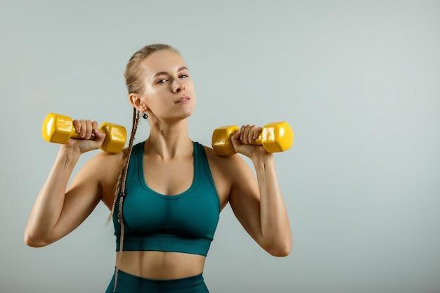 회색 배경, 피트니스 배너, 피트니스 동기 부여에 손에 아령을 들고 운동하는 여자. 회색 배경에 아령으로 운동하는 근육질 피트니스 모델의 사진.