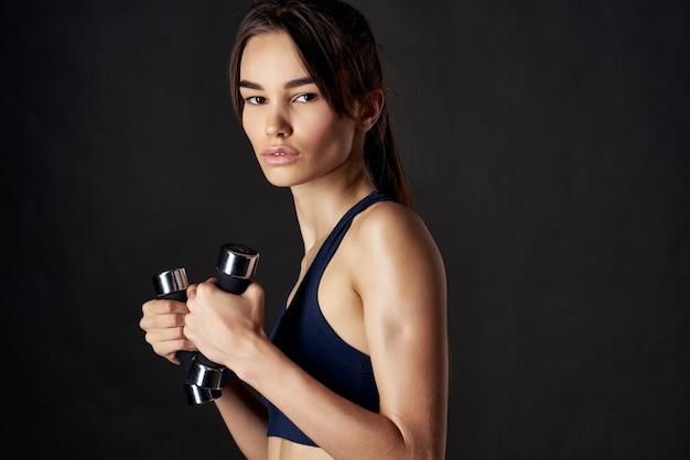手にダンベルを持つアスリート女性スリムな体型トレーニングの強さ