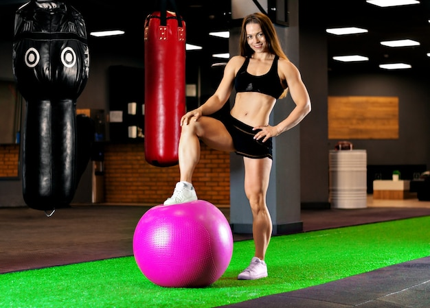 Спортивная (ый) женщина с ее ногой на фитнес-мяч
