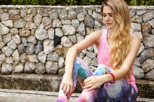 都市公園の舗装の上に座って、トレーニングから回復する長いブロンドの髪を持つ運動女性。