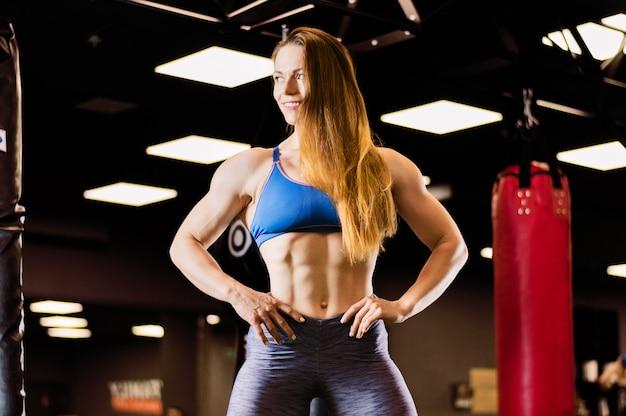 Спортивная (ый) женщина с длинными волосами позирует в тренажерном зале