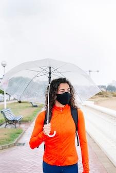 Спортивная (ый) женщина с маской и зонтиком вниз по улице