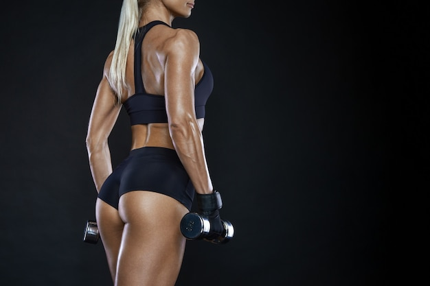 Athletic woman with muscular physique holding dumbbells