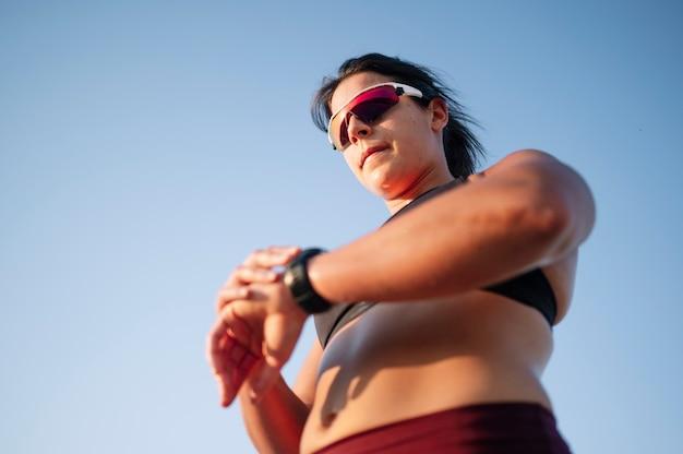 通りでスマートウォッチを持つ運動女性