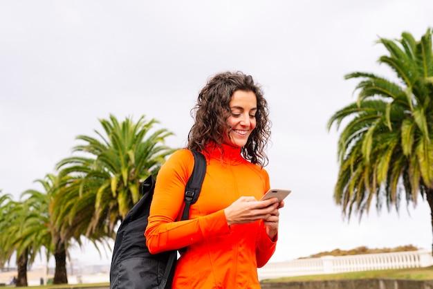 Спортивная (ый) женщина со спортивной сумкой и смартфоном на улице